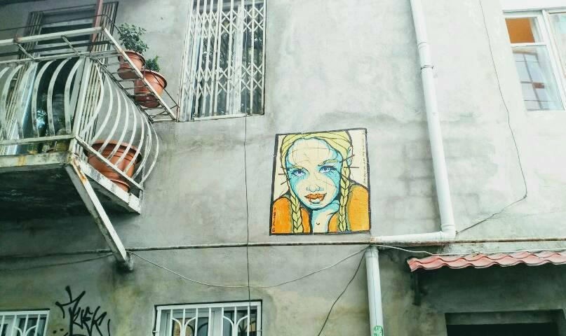 Gelbe Frau schaut von Hauswand